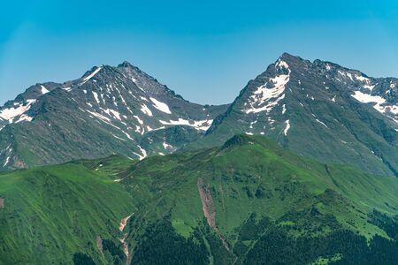 Hohe Berge mit grünen Hängen und schneebedeckten Gipfeln. Gebirgszüge im Sommer.