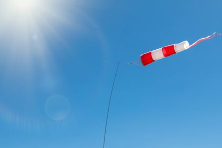 Windsock on a background of blue sky on a sunny day. High wind speed, strong wind.