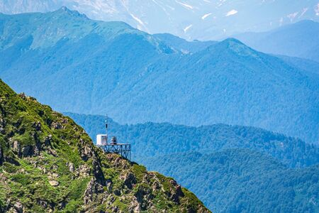 Anti-Avalanche Station and meteorological station at the top of a mountain range. Green vegetation in the summer in the mountains