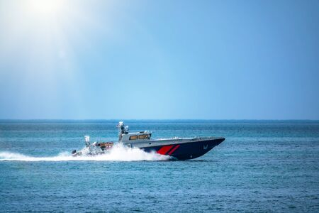A coast guard patrol boat sails near the shore on a clear sunny day.