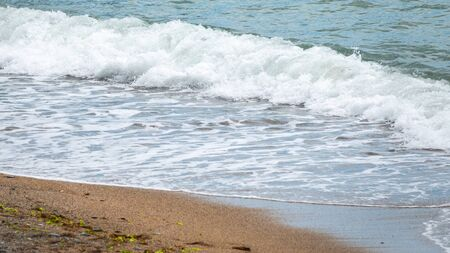 Soft wave of the sea on the sandy beach. Sea wave with foam
