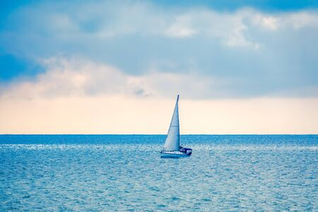 Sailing yacht in the blue calm sea. A yacht in peaceful waters. Banco de Imagens
