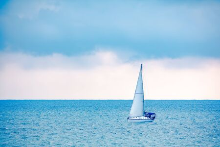 Sailing yacht in the blue calm sea. A yacht in peaceful waters. Stock Photo