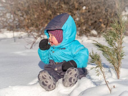 A small child sits in the snow at park. Infant sits in the snow in park at winter.