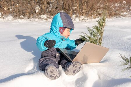 A small child sits in the snow with a laptop. Infant using laptop in park at winter