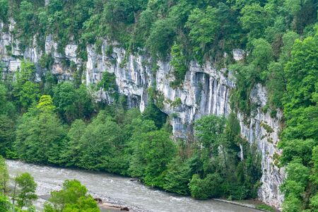 Mountain gorge with a river below. Canyon of mountain river on steep slopes, misty canyon, flashy river.