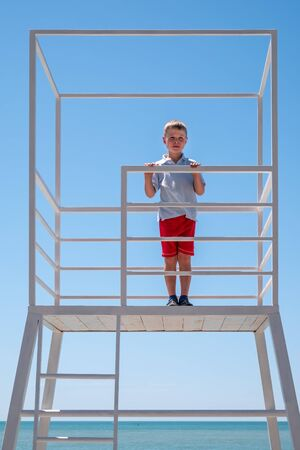 The boy stands in a rescue tower on the beach at sunny day