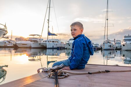 A boy in a blue jacket sits on a pier with yachts during sunset. Beautiful clear sunset in the sea harbor with moored yachts. Standard-Bild