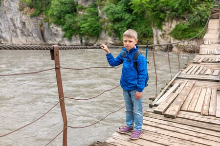 A boy with a backpack goes over a fast mountain river with rocky shores on a suspension bridge.