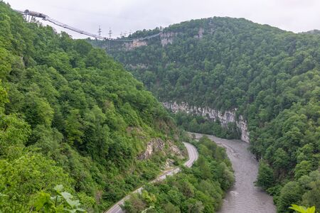 A gorge in the mountains with a suspension bridge over it. Skybridge suspension bridge over a precipice and river on a cloudy day. SkyPark, Sochi, Russia.