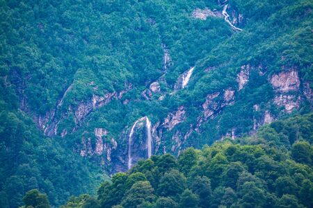 Green mountains with a high waterfall in spring or summer. Powerful stream of a mountain river among stones and rocks. 写真素材
