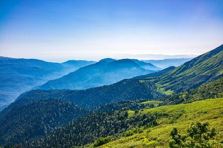 Uitzicht over de groene vallei, omgeven door hoge bergen op een zomerse zonsondergang. Lagen van bergen in de nevel tijdens zonsondergang. Meerlagige mistige zelfstandige naamwoorden. Bergen in de zomer.