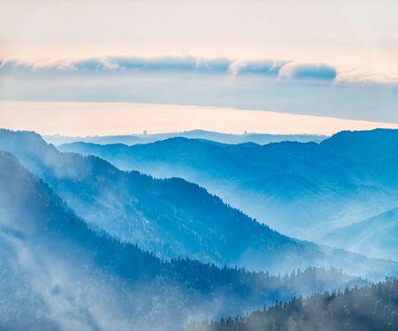Zielony stok górski. Warstwy gór w mgle podczas zachodu słońca. Wielowarstwowe rzeczowniki mgliste. Krasnaja Polana, Soczi, Rosja. Zdjęcie Seryjne