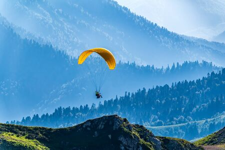 Yellow paraglider over the Green Mountain slope. Paraglider fly over mountain slope on sunny summer day, Imagens