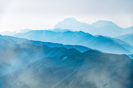 High mountains with green slopes in dense fog. Layers of mountains in the haze during sunset. Multilayered misty nountains. Krasnaya Polyana, Sochi, Russia. Standard-Bild