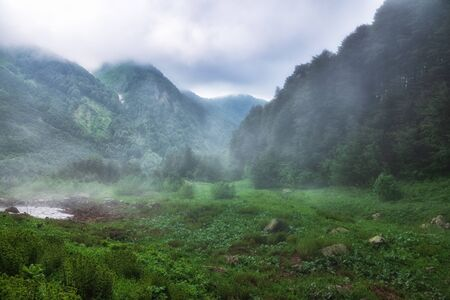 Green valley surrounded by mountains is covered in fog and clouds. Heavy fog in green misty mountains on a cloudy day. Achishkho ridge - the wettest place in Russia. Krasnaya Polyana, Sochi, Russia