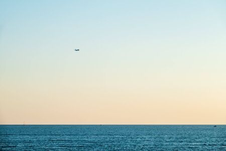 Silhouette of a landing plane over the blue sea at sunset. Airplane flying over sea water on sunset sky background. Ttravel aircraft silhouette Stock fotó