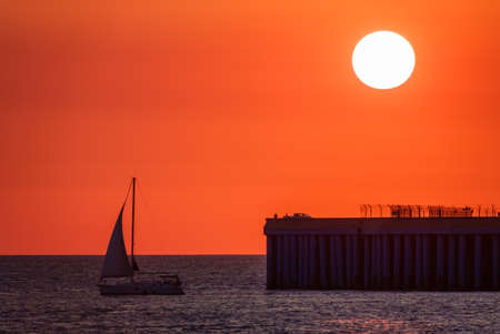 Beautiful red and orange sunset over the sea in a cloudy sky. The sun goes down over the sea. Dramatic Sunset Sky. Silhouette of a sailing yacht and a pier with fishermen at sunset