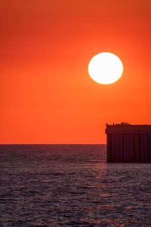 Beautiful red and orange sunset over the sea in a cloudy sky. The sun goes down over the sea. Colorfol Sunset Sky. Silhouette of a pier with fishermen at sunset