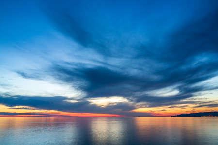 Beautiful orange sunset over the sea in a cloudy sky.