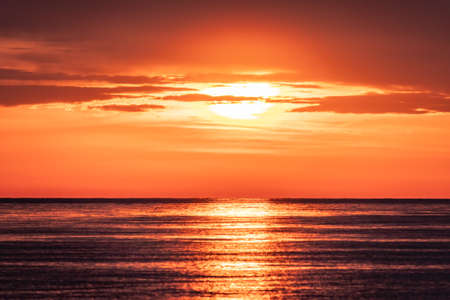 Beautiful red and orange sunset over the sea in a cloudy sky. Dramatic Sunset Sky. Bright sun silhouette sinks into the sea. Banco de Imagens - 155283605