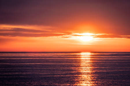 Beautiful red and orange sunset over the sea in a cloudy sky. Dramatic Sunset Sky Banco de Imagens - 155283610