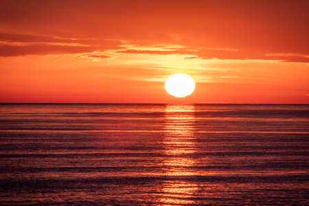 Beautiful red and orange sunset over the sea in a cloudy sky. The sun goes down over the sea. Dramatic Sunset Sky Banco de Imagens - 155283615