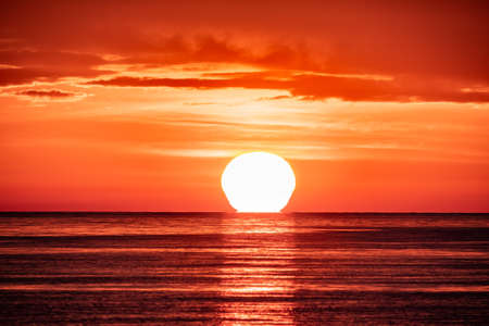 Beautiful red and orange sunset over the sea in a cloudy sky. The sun goes down over the sea. Dramatic Sunset Sky Banco de Imagens - 155283617