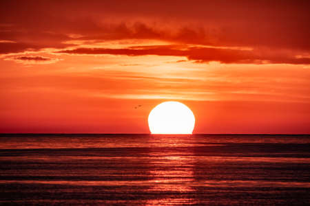 Beautiful red and orange sunset over the sea in a cloudy sky. The sun goes down over the sea. Two seagulls are flying against the sunset. Dramatic Sunset Sky Banco de Imagens - 155283619