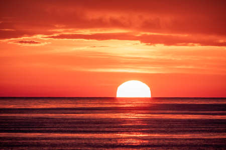 Beautiful red and orange sunset over the sea in a cloudy sky. The sun goes down over the sea. Dramatic Sunset Sky Banco de Imagens - 155283622