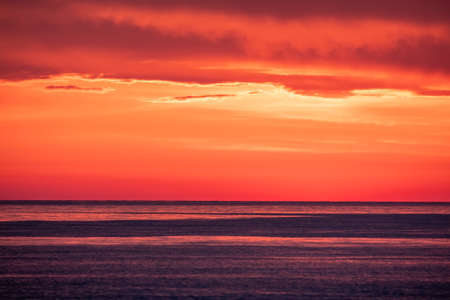 Beautiful red and orange sunset over the sea in a cloudy sky. Dramatic Sunset Sky Banco de Imagens - 155283623