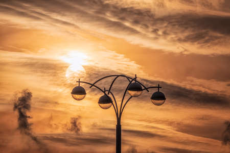 Street lamp on the background of the dramatic sunset sky with the silhouette of the sun Banco de Imagens - 155283725