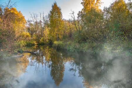 Autumn forest is reflected in the water of river with fog on the water Autumnal forest near the lake. Golden autumn colors. Banco de Imagens