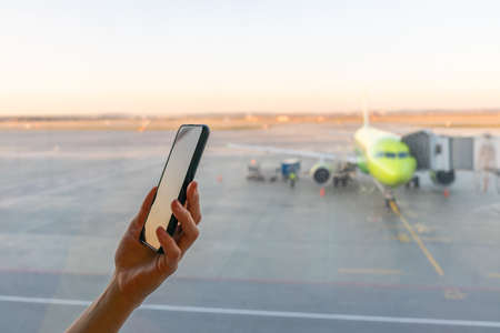 Close-up shot of female hand holding smart phone by window at airport. Area with airplane in background. Departure for vacation, waiting for the plane at the airport. Flight delay.