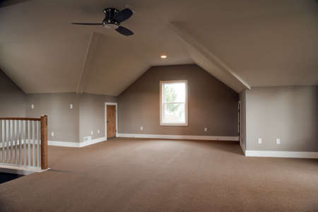 befejezetlen: Unfinished attic of a home. It is empty except for a ceiling fan in the center of the room. Horizontal shot.