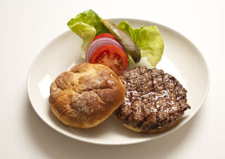 Plate holding a hamburger patty with lettuce, tomatoes and onions on the side. Horizontal shot.