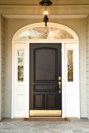 front door: Exterior front entrance of an upscale home with an illuminated porch light. Vertical format.
