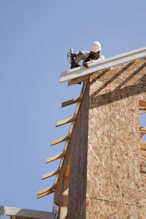 Low angle view of a construction worker attaching pieces to a partially built roof. Vertical shot. photo