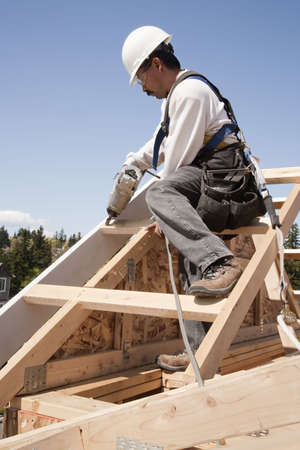 Construction worker fastening wooden beams on top of a partially built structure. Vertical shot. photo