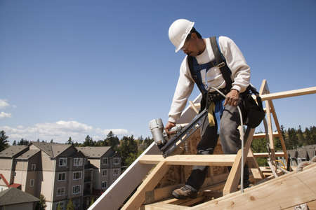 Construction worker fastening wooden beams on top of a partially built structure. Apartment buildings can be seen in the background. Horizontal shot. photo