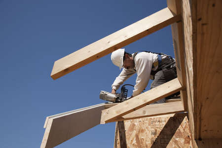 Construction worker fastening wooden beams on top of a partially built structure. Horizontal shot. photo