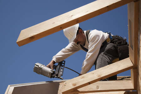 roof framing: Construction worker fastening wooden beams on top of a partially built structure. Horizontal shot.
