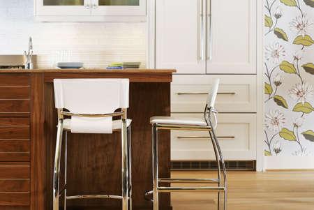 Cucina singolarmente decorata con sedie in un'isola nel mezzo. C'è una carta da parati a fiori sul muro. Tiro orizzontale
