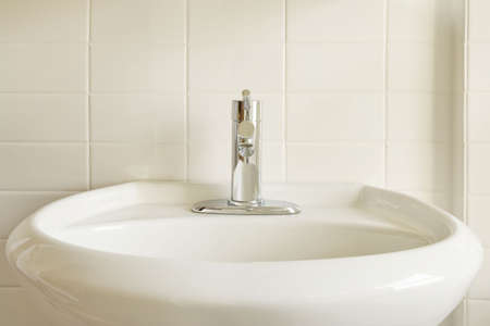 Close-up of a modern stainless steel faucet on an oval, white porcelain pedestal-style sink against a white tile wall. Horizontal format. photo