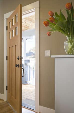 puerta abierta: Puerta de entrada a una casa que est� abierta. El porche delantero puede verse en la distancia. Un disparo vertical.  Foto de archivo