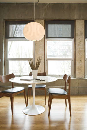 contemporary living room: Dining room table and chairs in a modern loft setting. Vertical shot. Stock Photo