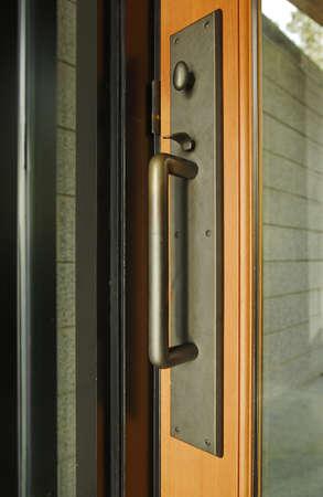 door knob: A brass door handle with turning lock knob and thumb latch. Vertical shot.
