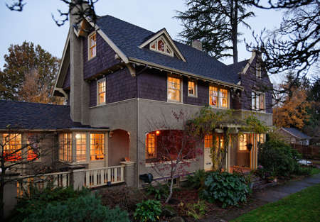 architectural exterior: Exterior view of a large home with lots of trees and greenery in the evening. Horizontal shot.