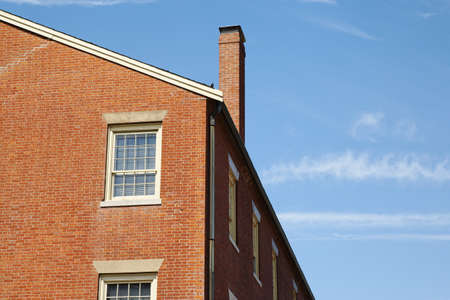 chimney corner: Low angle view of a brick building against a clear blue sky. A chimney is jutting out of the roof. Horizontal shot. Stock Photo