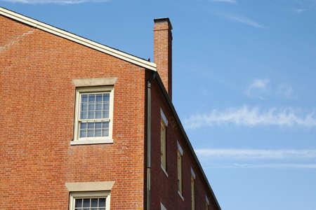 chimney corner: Vista de �ngulo bajo de un edificio contra un cielo azul claro de ladrillo. Una chimenea es el lado fuera del techo. Horizontal a tiros.